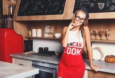 Cozinha atrativa loura de Smiling On The da dona de casa imagem de stock
