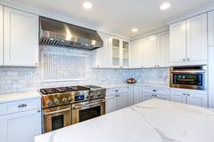 Cozinha branca com a capa de aço inoxidável sobre o cooktop do gás fotografia de stock