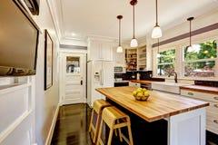 Cozinha branca com a ilha de madeira da parte superior contrária Imagem de Stock
