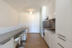 Cozinha branca com parquet em um estúdio fotos de stock royalty free