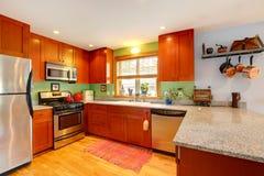 A cozinha com partes superiores do granito e a parte traseira do verde espirram imagens de stock