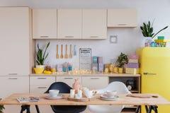 A cozinha de ano novo com um refrigerador amarelo e os pratos, uma árvore de Natal verde foto de stock royalty free