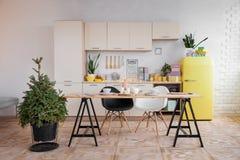 A cozinha de ano novo com um refrigerador amarelo e os pratos, uma árvore de Natal verde fotografia de stock