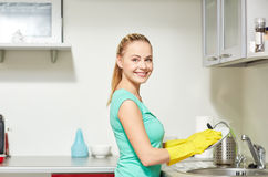Cozinha de lavagem dos pratos da mulher feliz em casa imagens de stock royalty free