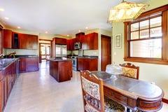 Cozinha de madeira do grande chery com tabela da sala de jantar. Foto de Stock Royalty Free