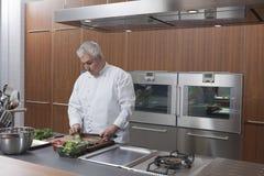 Cozinha do anúncio publicitário de Chopping Vegetables In do cozinheiro chefe fotos de stock