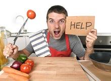 Cozinha do homem novo em casa no avental do cozinheiro desesperado em cozinhar o esforço Imagens de Stock