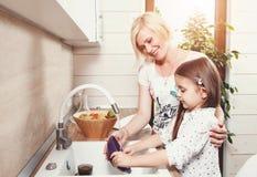 A cozinha do prato da lavagem da mãe e da filha fotos de stock