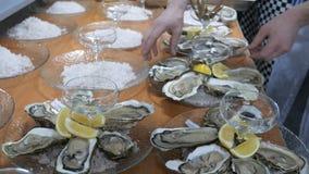 Cozinha do restaurante, muitas ostras em uma grande bandeja Localizado no gelo com limão Decorado antes de servir o convidado filme