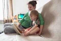 A cozinha feliz da mamã e do filho da família em casa leu junto o livro Fotografia de Stock