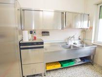 A cozinha industrial com refrigerador, máquina de lavar louça e afunda todo o st fotografia de stock