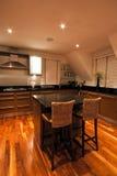 Cozinha luxuosa moderna com assentos no primeiro plano Imagens de Stock Royalty Free