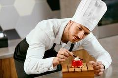 Cozinha masculina de Decorating Dessert In do cozinheiro de pastelaria fotografia de stock royalty free