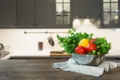 Cozinha moderna com os legumes frescos no tabletop de madeira, no espaço para você e nos produtos da exposição imagens de stock