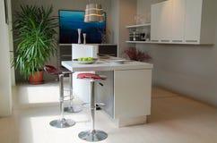 Cozinha moderna com tamboretes vermelhos imagens de stock royalty free