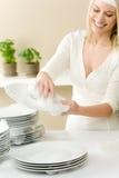 Cozinha moderna - pratos de lavagem da mulher feliz imagens de stock