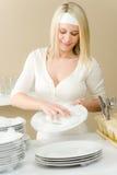 Cozinha moderna - pratos de lavagem da mulher feliz fotografia de stock