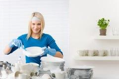 Cozinha moderna - pratos de lavagem da mulher feliz fotos de stock