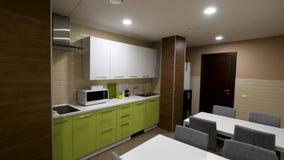 Cozinha pequena, moderna com armários verdes e dois tabels, comendo a zona para trabalhadores de escritório Simples e pequeno, no video estoque