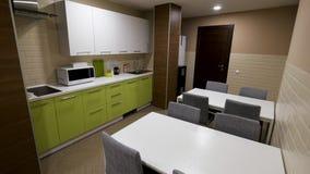 Cozinha pequena, moderna com armários verdes e dois tabels, comendo a zona para trabalhadores de escritório Simples e pequeno, no filme