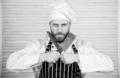 Cozinha perigosa cozinheiro chefe pronto para cozinhar homem seguro na faca da posse do avental e do chap?u alimento farpado dos  imagem de stock