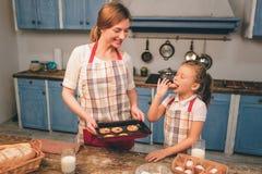 Cozinhando bolos caseiros A família loving feliz está preparando a padaria junto A menina da filha da mãe e da criança está cozin imagens de stock
