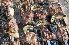 Cozinhando a carne em espetos sobre os carvões imagens de stock