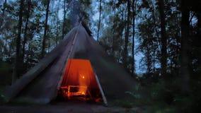 Cozinhando a carne roasted em uma tenda acolhedor na floresta escandinava escura filme