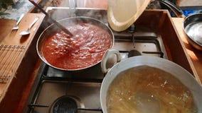 Cozinhando e agitando o molho de tomate para os espaguetes na frigideira filme