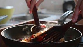 Cozinhando e agitando os espaguetes com molho de tomate vermelho na frigideira filme