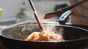 Cozinhando e agitando os espaguetes com molho de tomate vermelho na frigideira vídeos de arquivo