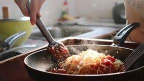 Cozinhando e agitando os espaguetes com molho de tomate vermelho na frigideira video estoque