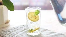 Cozinhando e derramando um vidro da água com limão, gelo e hortelã vídeos de arquivo