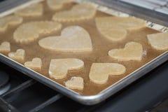 Cozinhando a folha com as cookies dadas forma coração que cozem Ontop um forno fotografia de stock