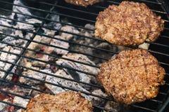 Cozinhando hamburgueres em carvões quentes com fumo imagem de stock