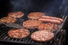 Cozinhando hamburgueres em carvões quentes com fumo Close-up imagem de stock royalty free