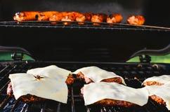 Cozinhando hotdogs e cheeseburgers em uma grade foto de stock
