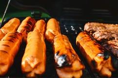 Cozinhando hotdogs e Hamburger em uma grade foto de stock