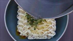 Cozinhando macarronetes imediatos, põe o ovo e os vegetais com sopa quente na bacia Conceito da comida lixo ou do fast food vídeos de arquivo