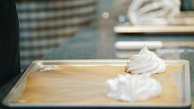 Cozinhando a merengue da sobremesa de Pavlova - tubo da pastelaria espalhe a merengue em uma folha de cozimento - tiro macro filme