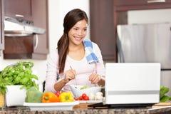 Cozinhando a mulher que usa o computador Fotos de Stock