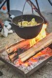 Cozinhando o alimento em um fogo em um caldeirão fotografia de stock royalty free