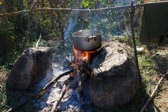 Cozinhando o alimento em uma fogueira em uma caminhada Imagens de Stock Royalty Free