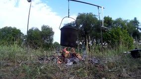 Cozinhando o alimento na fogueira no banco de rio video estoque