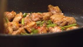 Cozinhando o alimento tailandês, picada Gaeng da almofada de Gai, em uma frigideira quente video estoque