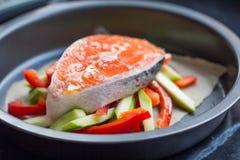Cozinhando o bife cru de salmões vermelhos dos peixes em vegetais, abobrinha Imagens de Stock Royalty Free