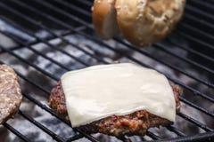 Cozinhando o cheeseburger em carvões quentes com fumo foto de stock royalty free