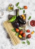 Cozinhando o fundo Ingredientes crus para fazer a massa - espaguete, beringela, tomates, pimenta, azeite, molho de tomate e manje foto de stock royalty free