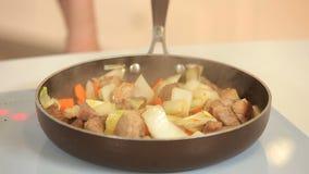 Cozinhando o guisado dos cubos e dos vegetais da carne de porco em uma frigideira filme
