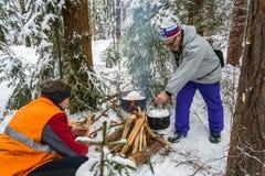 Cozinhando o jantar em um fogo em uma viagem do esqui, o 21 de fevereiro de 2016 Fotografia de Stock Royalty Free